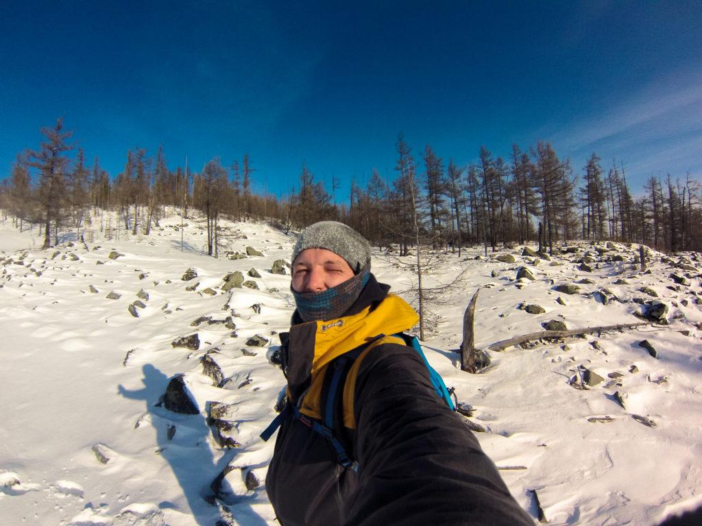 Алексей Забелин на фоне заснеженных камней на склоне Большого Саранакана