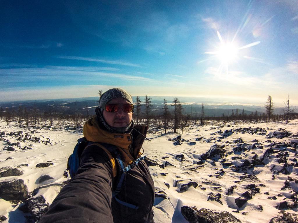 Алексей Забелин на фоне заснеженной долины реки Читинка