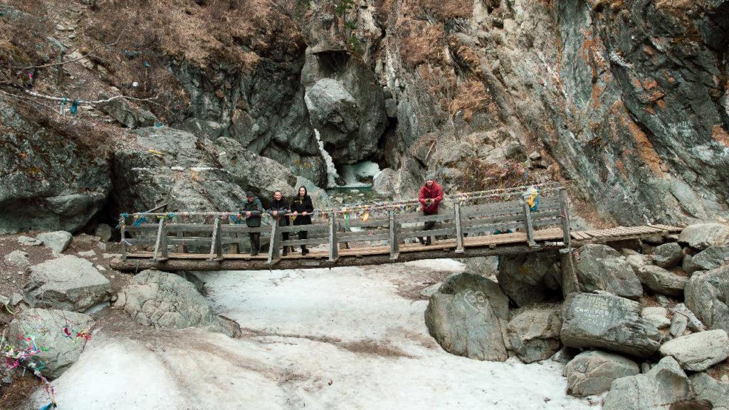 Мост через горную реку Кынгара с видом на водопад